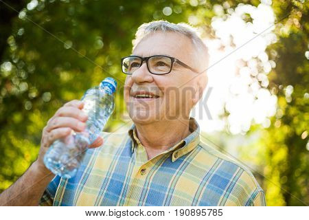 Happy senior man is drinking water in park.