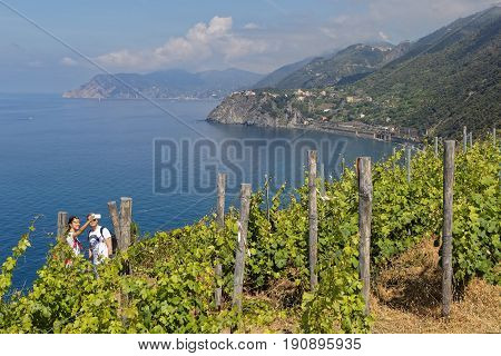 MANAROLA Italy June 3 2017 : A couple takes selfies on a nice landscape of the Cinque Terre National Park on the Italian Riviera. The Cinque Terre area is a very popular tourist destination and a world heritage site.