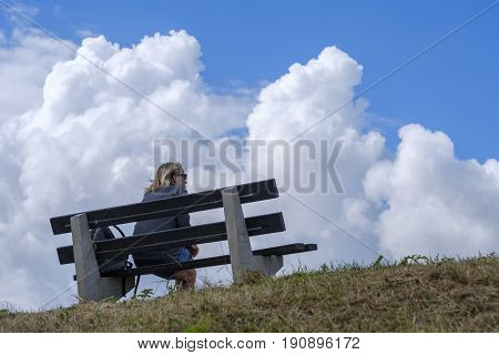 woman sitting on a bench rest and enjoy the view and how the cumulus clouds forming a storm