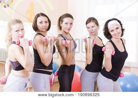 Sport Concepts and Ideas. Five Female Caucasian Athletes Standing with Barbrells Together in Sport Class.Horizontal Image Orientation