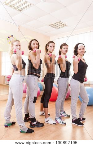 Sport Ideas. Five Female Caucasian Athletes Standing with Barbrells Together in Sport Class. Vertical Image Composition