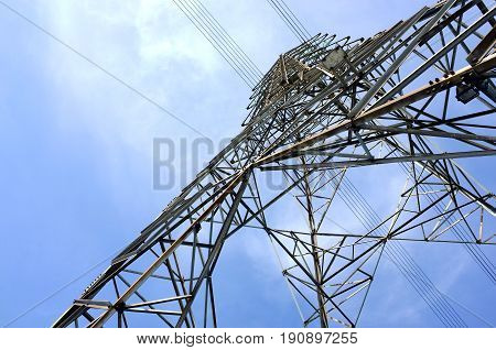 close-up uprisen angle steel frame of high voltage tower with electricity transmission power lines and blue sky