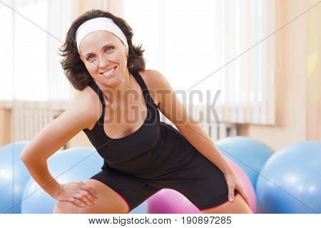 Sport Fitness Wellness and Lifestyle Ideas.Portrait of Female Caucasian Athlete In Good Fit Posing Against Fitballs in Gym.Horizontal Image