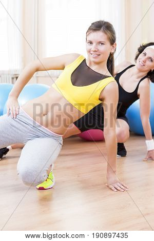 Sport Fitness Healthy Lifestyle Concepts.Two Female Caucasian Athletes in Good Fit Posing With Fitballs in Sport Gym.Vertical Orientation