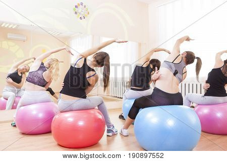 Sport Fitness Wellness and Helathy Lifestyle Concepts. Group of Five Caucasian Female Athletes Having Stretching Exercises with Fitballs Indoors.Horizontal Image Orientation