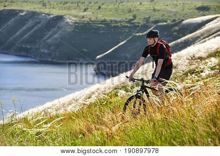 Attractive cyclist riding the bicyclist on the beautiful summer mountain trail. Young sportsman in the black sportwear, with helmet and backpack. Horizontal photo with beautiful landscape. Concept of the healthy and active lifestyle.