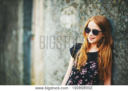 Outdoor fashion portrait of happy red-haired girl wearing sunglasses and old school style dress