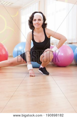 Fitness Wellness and Lifestyle Ideas.Portrait of Female Caucasian Athlete In Good Fit Posing Against Fitballs in Gym.Vertical Orientation