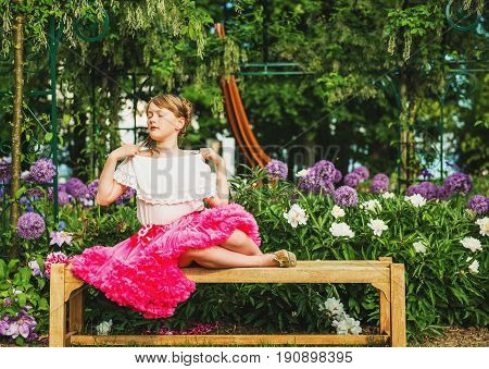Funny little girl resting on the bench in a beautiful flower garden on a nice summer day wearing white shirt and bright pink tutu skirt
