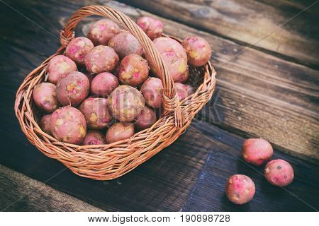 Raw potatoes in a brown wicker basket on a wooden background top view