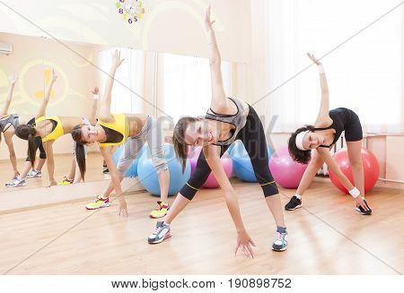 Fitnes and Stretching Conceots and Ideas. Three Happy Caucasian Female Athletes in Good Fit Having Stretching Exercises in Gym.Horizontal Image