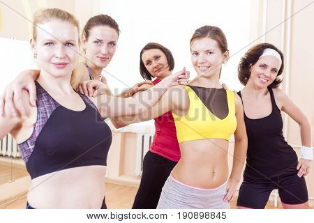 Sport and Healthy Lifestyle Concepts. Closeup Portrait of Five Happy Caucasian Female Athletes Posing Together Embraced Against Fitballs in Gym.Horizontal Shot