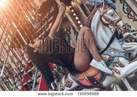 Just going round... Attractive young mixed raced woman in red bikini riding merry-go-round