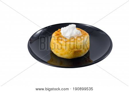Fried quark cheese pancake with sour cream on the top on a black plate.