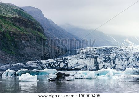 Evening landscape with ice floes in the glacial lake Fjallsarlon. Vatnajokull National Park, Iceland, Europe. Amazing tourist attraction. Art processing of photographs, color toning