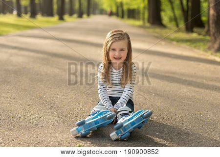 Long haired girl sitting on earth, resting from roller skating, in the green park