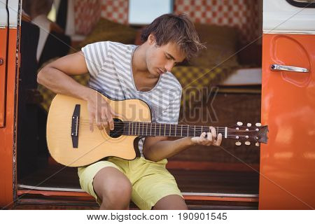 Young man playing guitar while sitting in motor home at forest