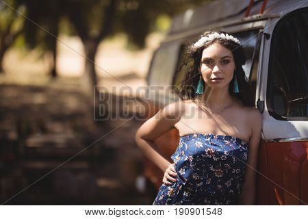 Portrait of young woman standing by motor home at forest
