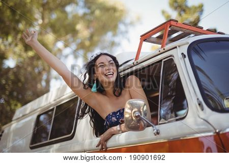Haooy woman leaning on window of motor home at forest