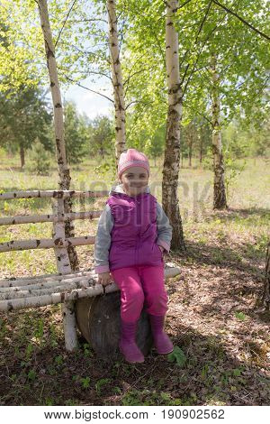 Little girl is sitting on a bench in a spring grove