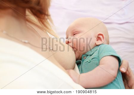 indoor portrait of mother breast feeding and hugging her baby