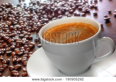 Freshly made tasty espresso cup of coffee with coffee beans on dark background