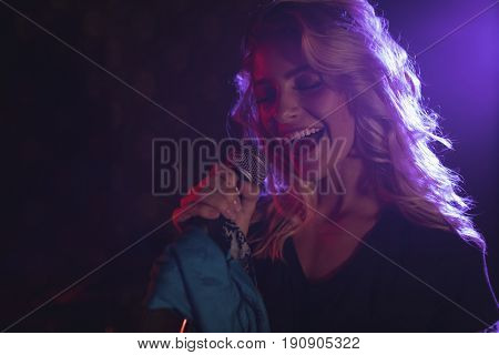 Close up of cheerful female singer performing in illuminated nightclub