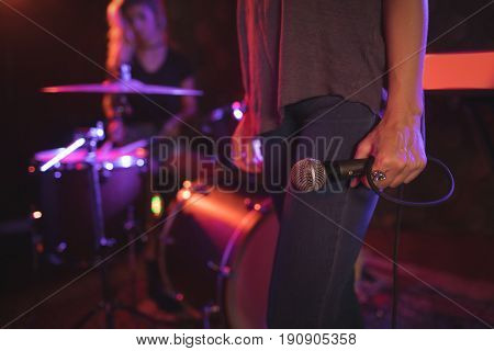 Low section of female singer holding microphone with drummer performing in illuminated nightclub