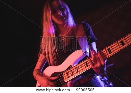 Low angle view of beautiful female guitarist performing in nightclub