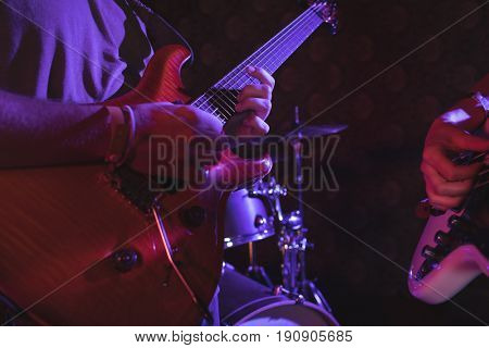 Mid section of guitarist performing in nightclub