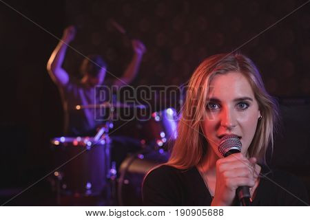 Portrait of female singer performing with male drummer in nightclub
