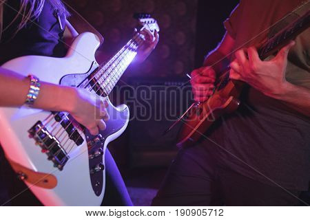 Mid section of male and female guitarist performing in nightclub