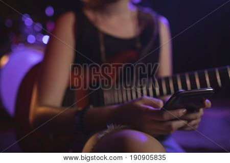Mid section of female guitarist using mobile in nightclub