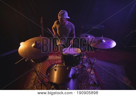 High angle view of male drummer performing in nightclub