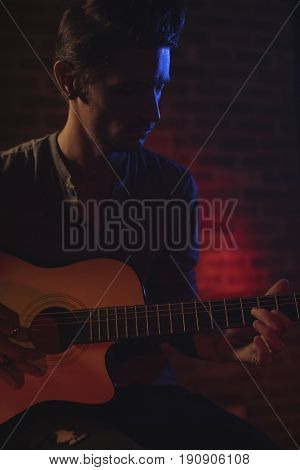 Close up of male guitarist playing guitar in nightclub