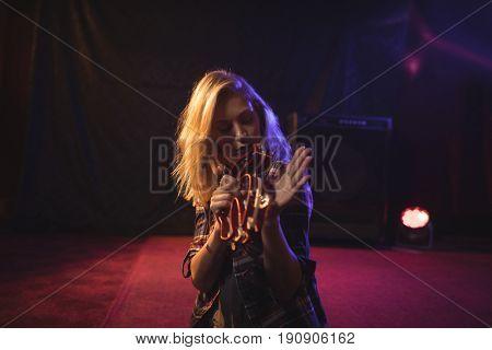 Young female musician playing tambourine in nightclub