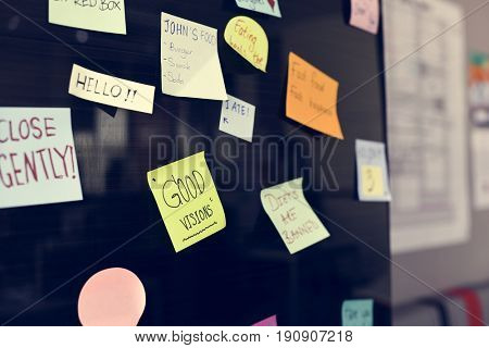 Sticky note reminder on bulletin board
