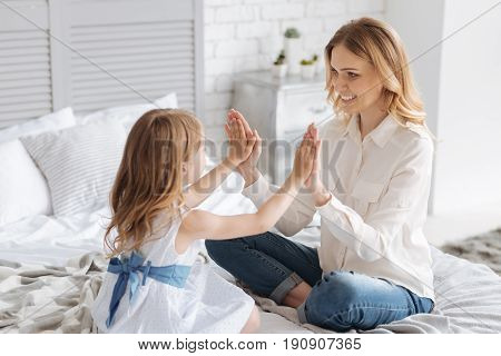 Quality time. Happy young mother and her lovely little daughter sitting on the bed and playing a pat-a-cake game for children via pressing their palms against one another