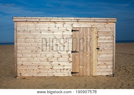 Unpainted beach hut. New wooden shed in the sunshine on the sand. Bare pine wood panelling on this new build cabin.