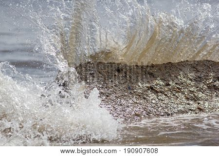 Force of nature. Splashing wave energy. Splash as sea water hits concrete rock. Fast shutter speed freezes water splashing. Image connotations of natural energy and coastal erosion.