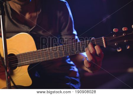 Mid section of male guitarist performing at music concert