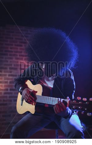 Male guitarist with frizzy hair performing at music concert