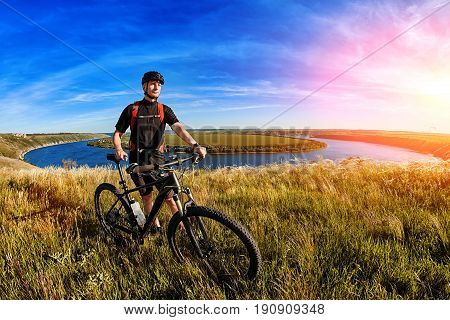 Attractive mountain cyclist stands on the hill above the beautiful river. Sportsman in the black sportwear, with helmet and backpack. Horizontal photo and fisheye. Beautiful landscape. Concept of the healthy lifestyle.