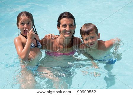 Thirty-year-old Mother With Two Children In The Pool Water In Summer