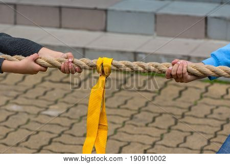 Children pulling the rope - close up on hands of young competitors