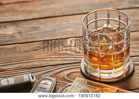Glass of whiskey or alcohol drink with ice cubes and car key on rustic wooden table with copy-space. Drink and drive and alcoholism concept. Safe and responsible driving concept.