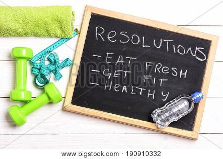 Resolutions like eat fresh get fit and healthy handwritten on blackboard near water bottle green dumbbells towel and cyan measure tape on white wood background top view. Sports and health concept