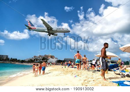 St Maarten Netherlands - February 13 2016: beach observe low flying airplanes landing near Maho Beach on island of St Maarten in the Caribbean
