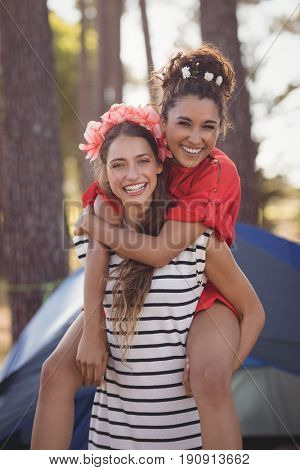 Portrait of cheerful woman piggybacking her female friend against tent at forest