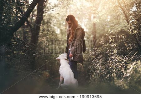 young woman with labrador retriever dog puppy during sunset in the forest